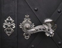 Decorative door handle. Closeup of decorative silver colored handle on dark door Royalty Free Stock Photography