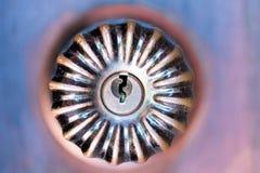 Decorative door knob on wood door. Close up old decorative door knob on wood door. Detail of a aged round ball door knob on brown door Stock Photography