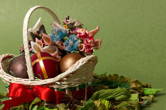 Decorative Easter basket with bow and eggs. Decorative basket with Easter eggs and beautiful arificial flowers on green background Royalty Free Stock Photos