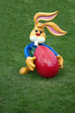 Decorative Easter bunny holding a big red egg Royalty Free Stock Image