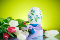 Decorative easter egg with a bouquet of spring tulips Stock Photos