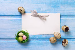 Decorative Easter eggs and empty tag on blue  wooden background. Stock Photo