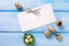 Decorative Easter eggs and empty tag on blue  wooden background. Royalty Free Stock Photography