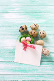 Decorative Easter eggs and empty tag on  turquoise wooden backgr Royalty Free Stock Image