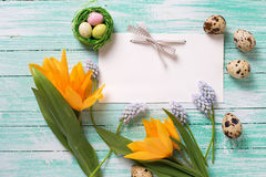 Decorative Easter eggs, flowers and empty tag on wooden backgrou Stock Image