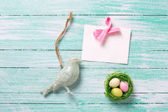 Decorative Easter eggs in nest , bird  and empty tag on wooden b Royalty Free Stock Image