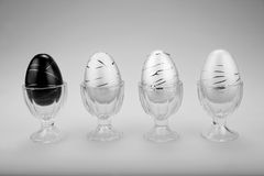 Decorative Easter Eggs in a Row - B&W. Decorative Easter eggs in cups in a row. One Black alongside three white on a gray background. Presented in Black and stock photo