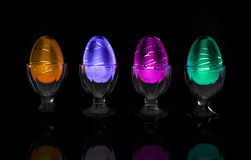 Decorative Easter Eggs in a Row - On Black. Decorative neon colored Easter eggs in cups in a row on a Black background stock images