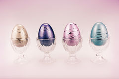 Decorative Easter Eggs in a Row - Retro. Decorative Easter eggs in cups in a row in pastel colours. Toned for a vintage retro faded look stock photography