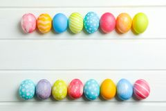Decorative Easter eggs on white wooden background, space for text stock images