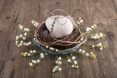 Decorative Easter nest on oak table with egg and spring flowers. Decorative Easter nest on oak table with duck egg and lily of the valley flowers Royalty Free Stock Images
