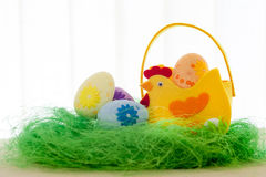 Decorative eggs on green grass. Chicken basket. Concepts Easter, eggs, hand made morning Stock Image