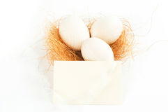 Decorative eggs lying on some hay with white ribbo Stock Images