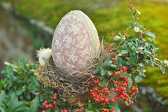 Decorative eggs in the nest. Easter egg in nest at a garden stock photo