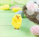 Decorative toys eggs in the nest. Decorative eggs toys in the nest and tulips for Easter on thelight  green background. Copy space, top view concept of Easter Stock Photography
