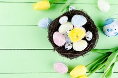 Decorative toys eggs in the nest. Decorative eggs toys in the nest and tulips for Easter on thelight  green background. Copy space, top view concept of Easter Stock Images