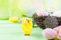 Decorative toys eggs in the nest. Decorative eggs toys in the nest and tulips for Easter on thelight  green background. Copy space, top view concept of Easter Stock Image
