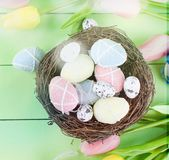 Decorative toys eggs in the nest. Decorative eggs toys in the nest and tulips for Easter on thelight  green background. Copy space, top view concept of Easter Royalty Free Stock Image