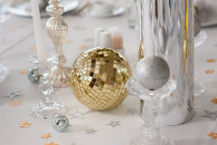 Decorative elements on the holiday table. Mirror ball and other decorative elements on a white tablecloth Royalty Free Stock Image