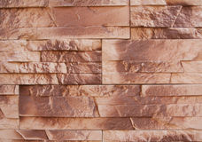Decorative facing stone. Stone wall texture of burnt brown color in some areas background Royalty Free Stock Photos