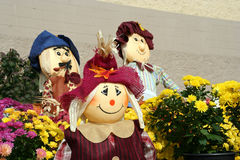 Decorative fall scarecrows. A trio of decorative fall scarecrows sitting among Chrysanthemums in an outdoor garden display. These cute decorative scarecrows are Stock Photos