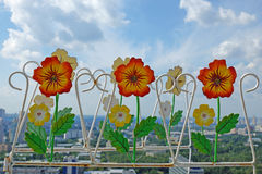 Decorative fence with flowers on sky background Stock Photo