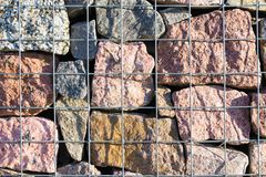 Decorative fence made from rocks behind wires stock photography