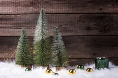 Decorative fir trees, golden and green balls, green candleholder and fairy lights on white fur background against vintage wooden. Wall. Minimalistic winter royalty free stock images