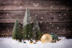 Decorative fir trees, golden and green balls and fairy lights on white fur background against vintage wooden wall stock photo