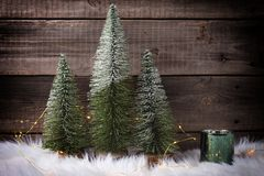 Decorative fir trees, green candleholder and fairy lights on white fur background against vintage wooden wall. Minimalistic winter holidays decoration stock images