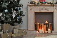 Decorative fireplace and Christmas tree with gift boxes. In stylish living room interior royalty free stock photography