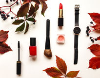 Decorative flat lay composition with cosmetics, woman accessories and autumn leaves and berries. Flat lay, top view royalty free stock photos
