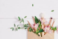 Decorative flat lay composition with makeup products, kraft envelope and flowers. Flat lay, top view on white background stock images