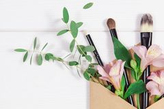 Decorative flat lay composition with makeup products, kraft envelope and flowers. Flat lay, top view on white background. Copytext Stock Photos