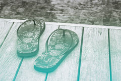 Decorative floral slip slops on a pool deck. Decorative floral slip slops on a wooden pool deck overlooking the mottled blue-green water conceptual of a summer Royalty Free Stock Images