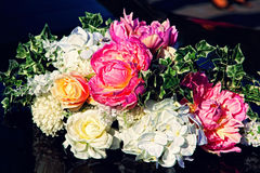 Decorative flowers bouquet on black wedding car. Royalty Free Stock Photos