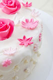Decorative flowers on a cake. Pink decorative fondant flowers on a white cake Royalty Free Stock Images