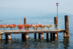 Decorative flowers on pier. Scenic view of decorative flowers on pier with Gardone Riviera coastline in background, Brescia, Lombardy, Italy Royalty Free Stock Photography