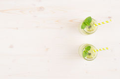 Decorative frame of freshly blended green kiwi fruit smoothie in glass jars with straw, mint leaf, top view. Stock Photo