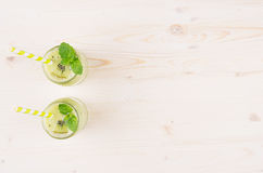 Decorative frame of freshly blended green kiwi fruit smoothie in glass jars with straw, mint leaf, top view. White wooden board background, copy space Stock Image