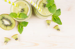 Decorative frame of green kiwi fruit smoothie in glass jars with straw, mint leaf, cute ripe berry, top view. Stock Images