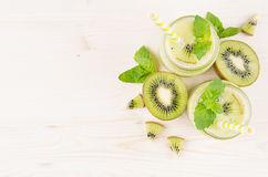 Decorative frame of green kiwi fruit smoothie in glass jars with straw, mint leaf, cute ripe berry, top view. Royalty Free Stock Photo