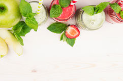Decorative frame green and red fruit smoothie  in glass jars with straw, mint leaves, of strawberry and apples, top view. White wo Stock Photography