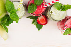 Decorative frame green and red fruit smoothie in glass jars with straw, mint leaves, of strawberry and apples, top view. Stock Photos