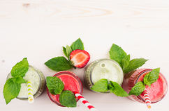 Decorative frame green and red fruit smoothie  in glass jars with straw, mint leaves, of strawberry and apples, top view. Royalty Free Stock Image