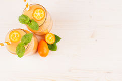 Decorative frame of orange citrus kumquat  fruit smoothie in glass jars with straw, mint leaf, cute ripe berry, top view. Royalty Free Stock Image