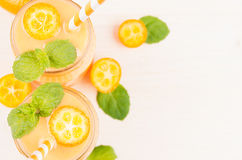 Decorative frame of orange citrus kumquat fruit smoothie in glass jars with straw, mint leaf, cute ripe berry, top view. Stock Photo