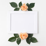 Decorative frame with orange roses and green leaves. Flat lay. Top view Stock Photography