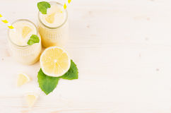 Decorative frame of yellow lemon smoothie in glass jars with straw, mint leaf, cut lemon, top view. Royalty Free Stock Images