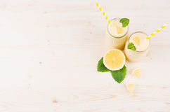 Decorative frame of yellow lemon smoothie in glass jars with straw, mint leaf, cut lemon, top view. Royalty Free Stock Image
